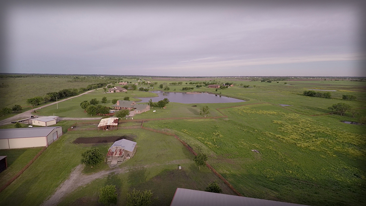 Lonesome Dove Ranch - Aerial of the western style salon, outdoor pin, and turnout pasture