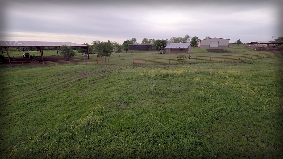Lonesome Dove Ranch - Aerial of the western style salon, outdoor pin, hay barn, riding arena and turnout pasture